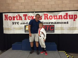 Mike and son at a fencing tournament